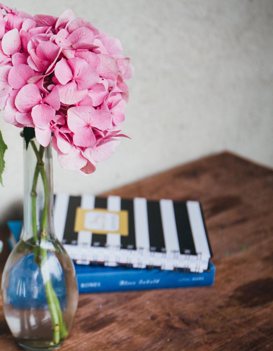 Trendfarbe Beton mit pinker Blume auf Holztisch