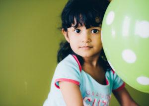 Mädchen mit grünem Luftballon vor grüner Wand