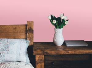 Holzbett vor rosa Wand
