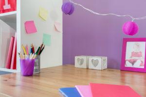 Kinderzimmerschreibtisch vor lila Wand