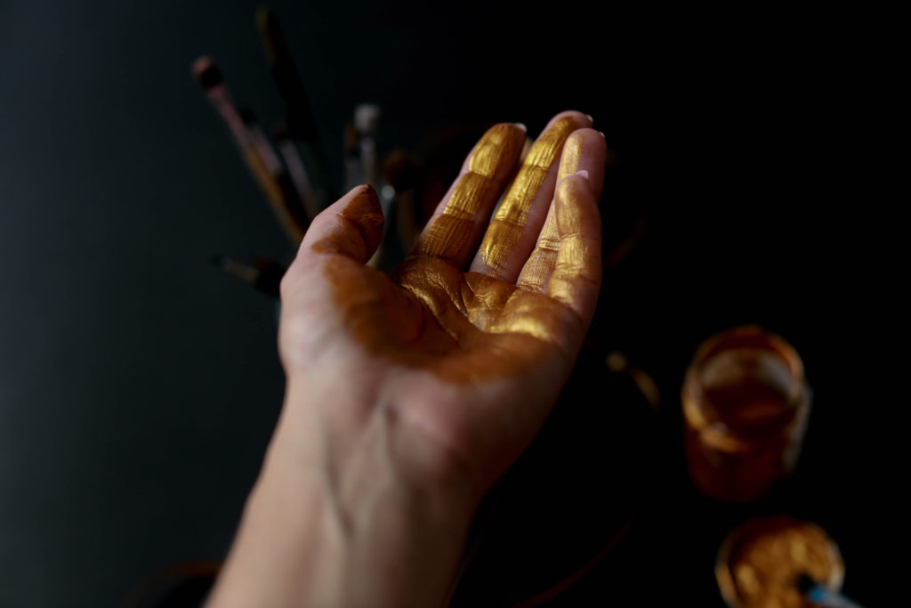 Reaching hand with golden color on it