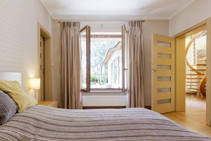 Schlafzimmer mit offenem Fenster zum Stoßlüften