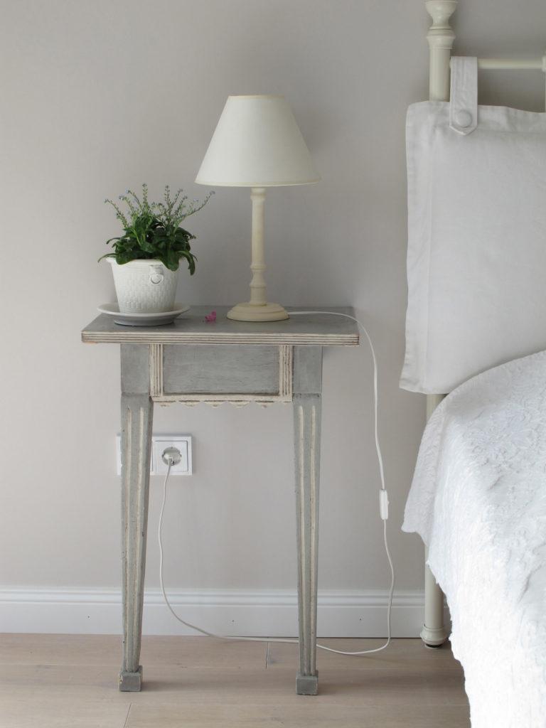 Bett mit Nachttisch an Wand