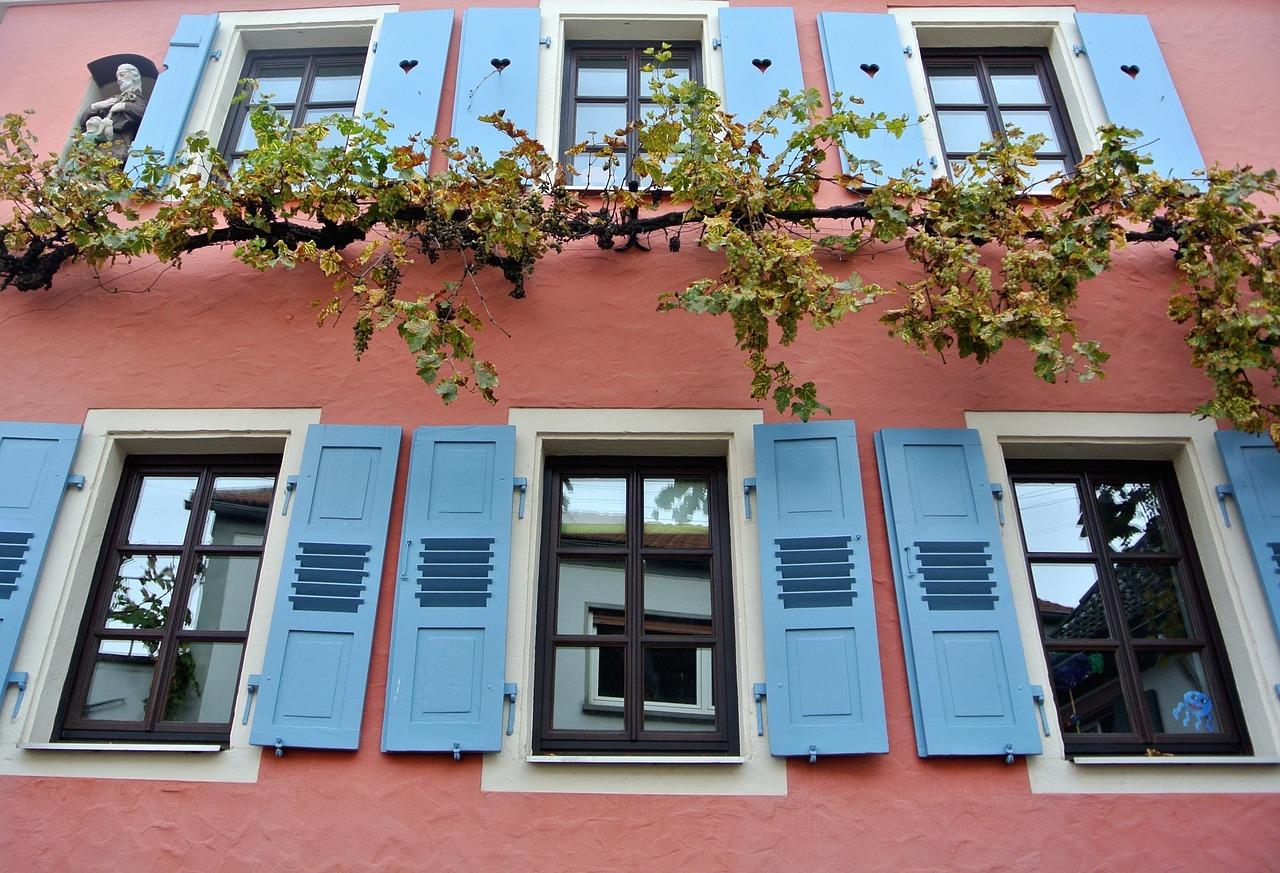 Pinkes Haus mit blauen Fensterläden